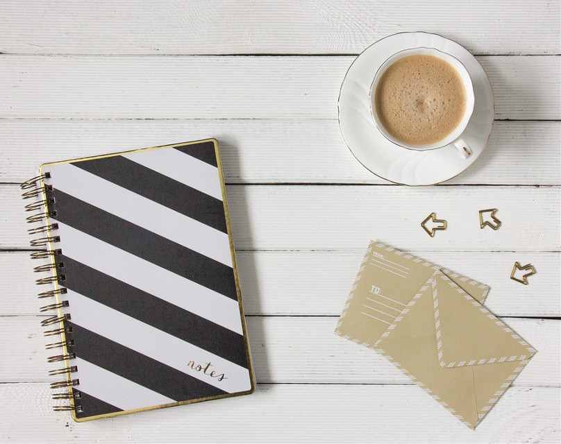 Pour your imagination into this cup of coffee and take this shot to the next level.  Pixabay  (Public Domain)  #FreeToEdit #coffee #notebook #envelopers #white #write #workdesk
